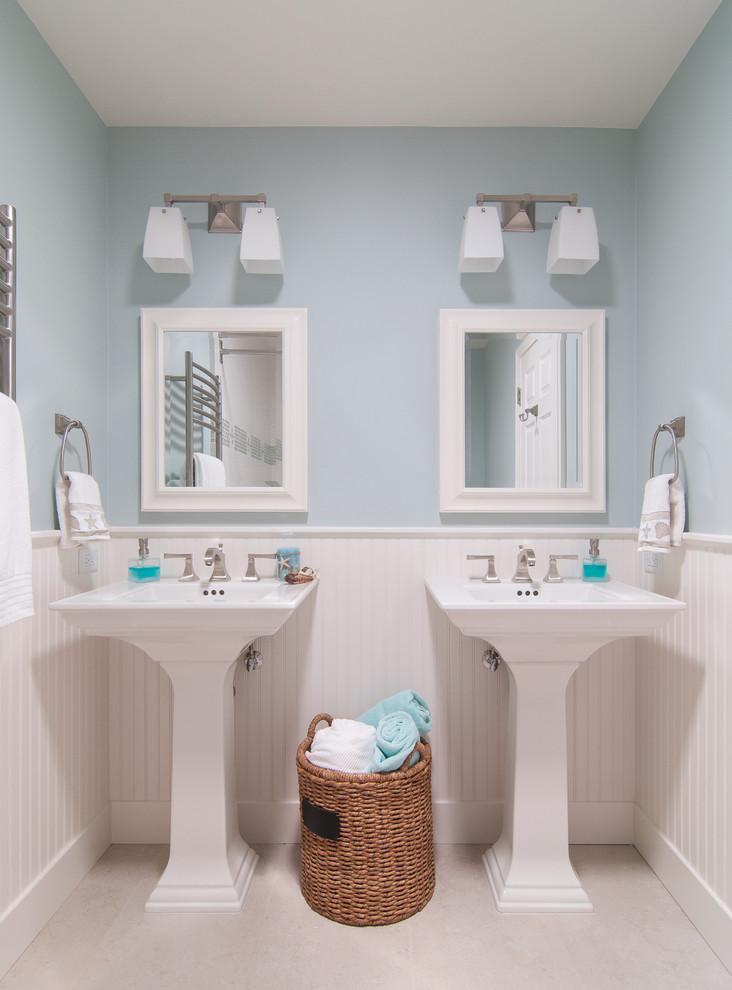 Wicker basket between twin pedestal basins in duck egg blue bathroom