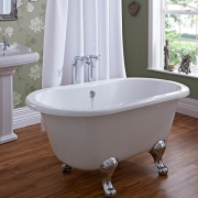 Small traditional freestanding bathtub in centre of a wooden floored bathroom, with traditional toilet and basin.