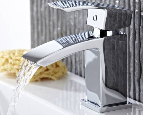 modern chrome basin tap with water pouring from spout