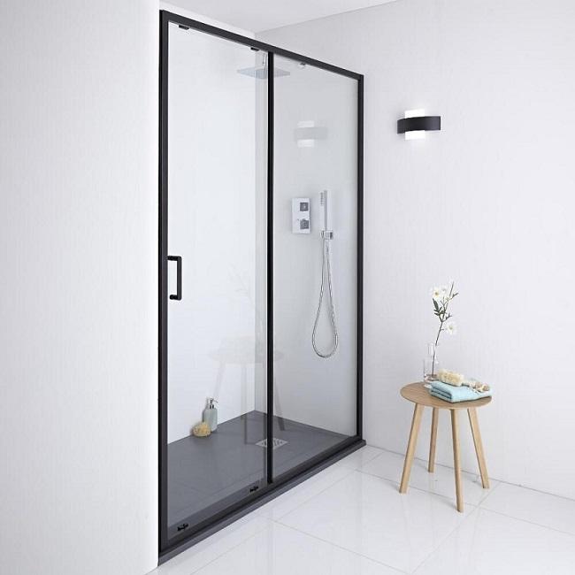 Recess shower with black-framed sliding shower door and shower tray