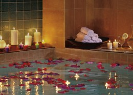 red rose petals and candles suggest the health benefits of a hot bath