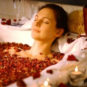 woman relaxing in a bath with scented flower petals