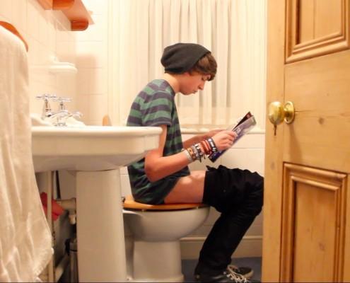 Boy on toilet with door open