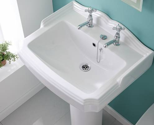 traditional basin with chrome taps against a turquoise wall